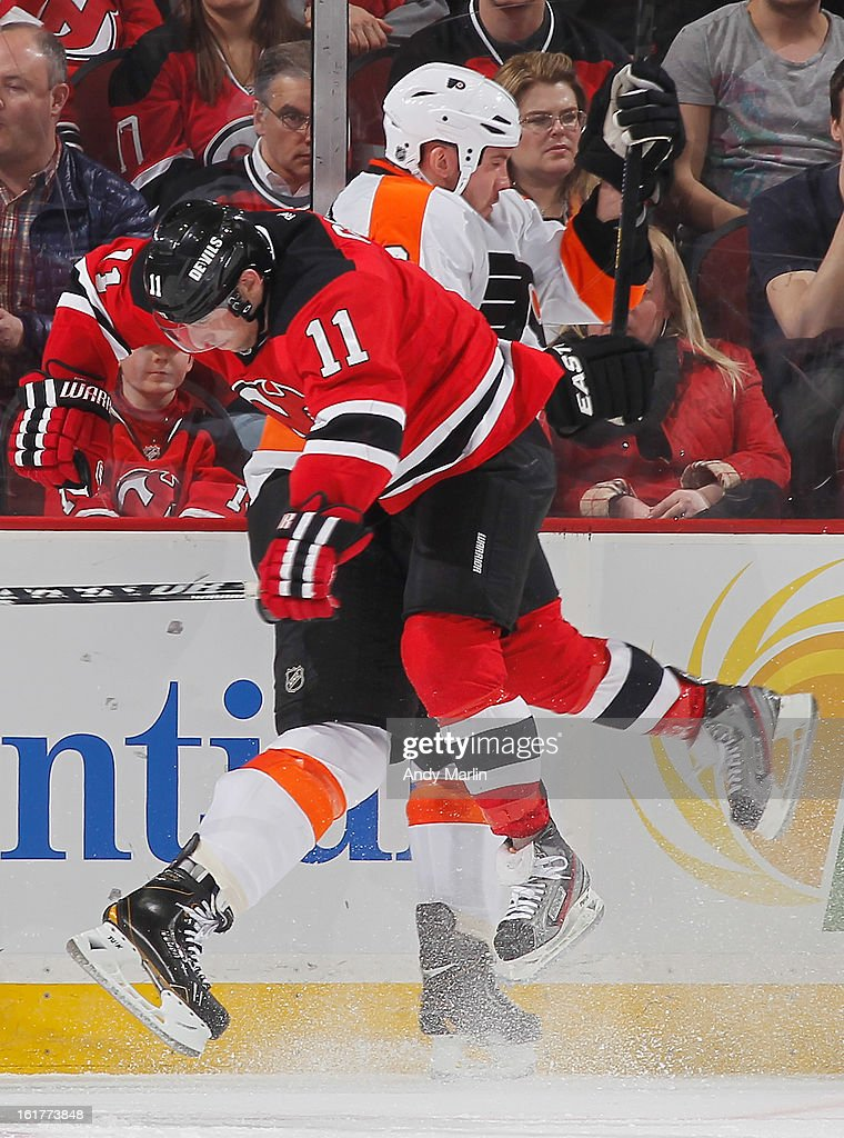 Nicklas Grossmann #8 of the Philadelphia Flyers is checked into the boards by Stephen Gionta #11 of the New Jersey Devils during the game at the Prudential Center on February 15, 2013 in Newark, New Jersey.