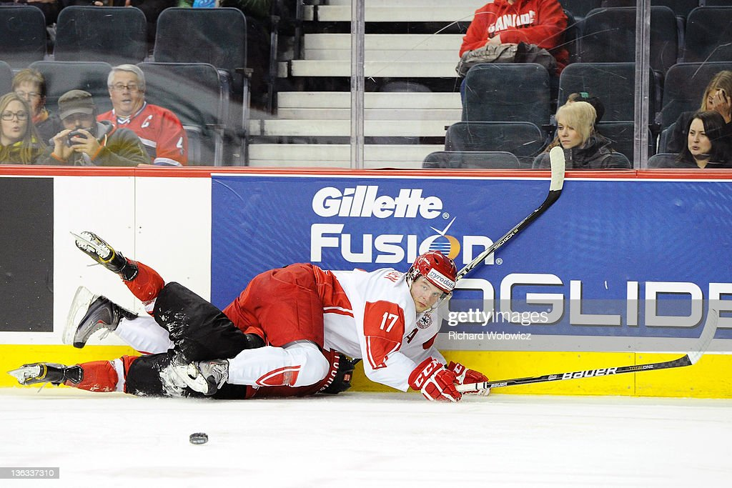Nicklas Jensen #17 of Team Denmark falls to the ice after body checking Lino Martschini #12 of Team Switzerland during a relegation game at the 2012 World Junior Hockey Championships at the Saddledome on January 2, 2012 in Calgary, Alberta, Canada.