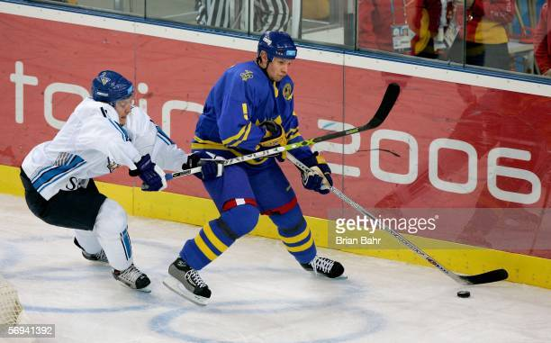Nicklas Lidstrom of Sweden tries to keep the puck away from Saku Koivu of Finland during the final of the men's ice hockey match between Finland and...