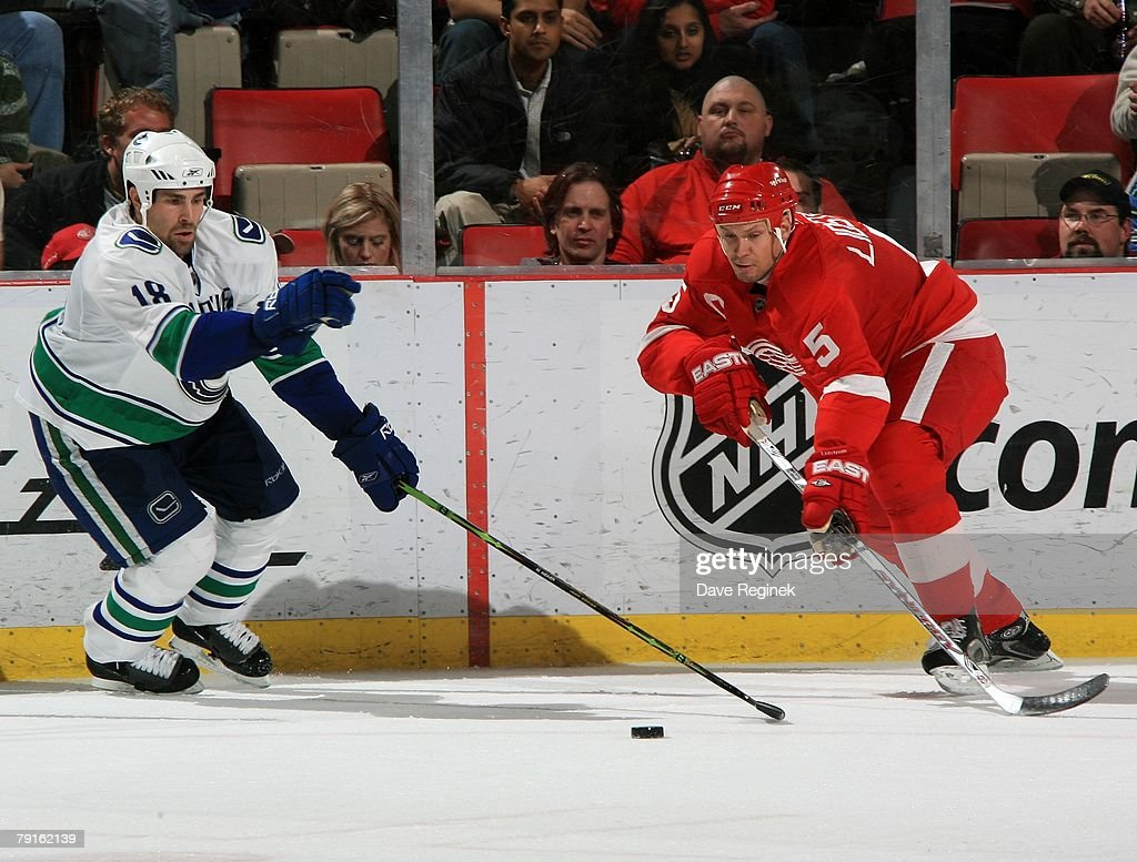 Nicklas Lidstrom of the Detroit Red Wings Mike Weaver of the Vancouver Canucks go after the loose puck during a NHL game on January 17 2008 at Joe...