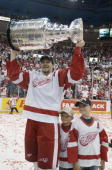 Nicklas Lidstrom of the Detroit Red Wings raises the Stanley Cup as he celebrates with his sons Adam and Kevin after eliminating the Carolina...