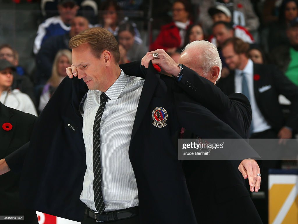Nicklas Lidstrom receives his Hockey Hall of Fame blazer from the Chairman of the Hockey Hall of Fame Lanny McDonald prior to the Legends Classic...