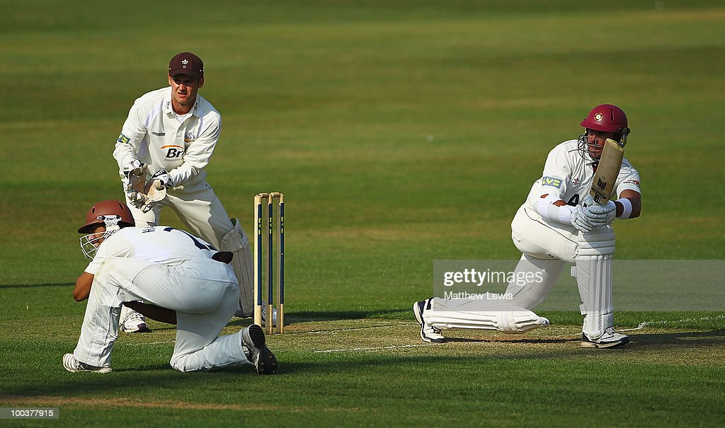 Nicky Boje of Northamptonshire hits the ball towards the boundary, as Steve Davies and Arun Harinath of Surrey looks on during the LV County Championship match between Northamptonshire and Surrey at the County Ground on May 24, 2010 in Northampton, England.