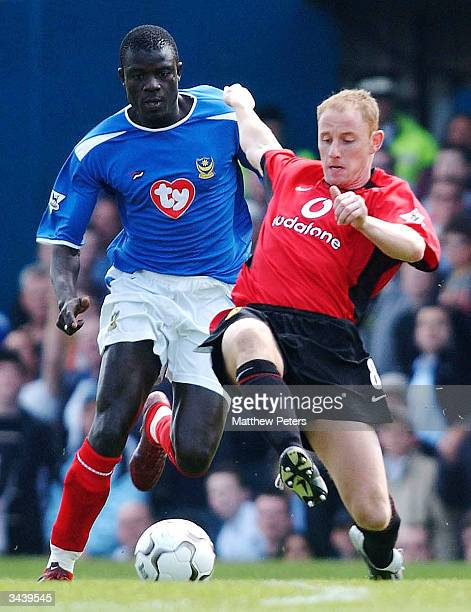 Nicky Butt of Manchester United challenges Amdy Faye of Portsmouth of the ball during the FA Barclaycard Premiership match between Portsmouth and...