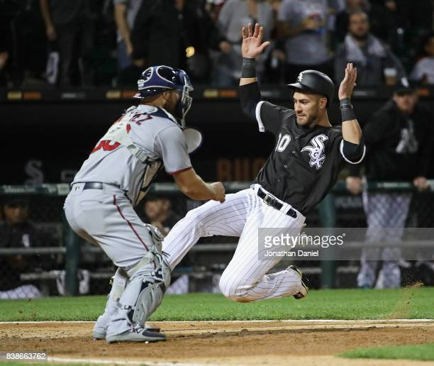 Nicky Delmonico of the Chicago White Sox dives in to score a run in the 6th inning past Chris Gimenez of the Minnesota Twins at Guaranteed Rate Field...