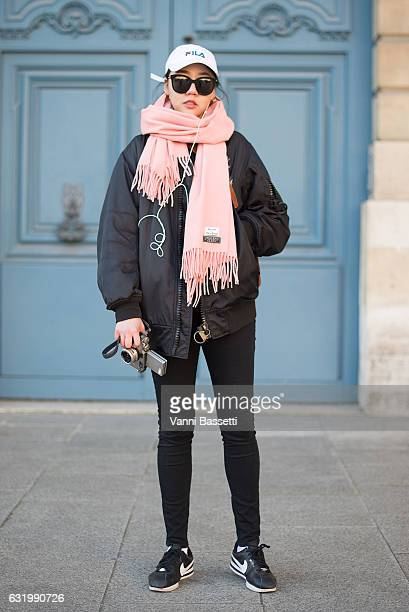 Nicky Zeng poses wearing a KTZ bomber jacket Acne Studios scarf and Nike Cortez shoes before the Balenciaga show in Place Vendome during Paris...