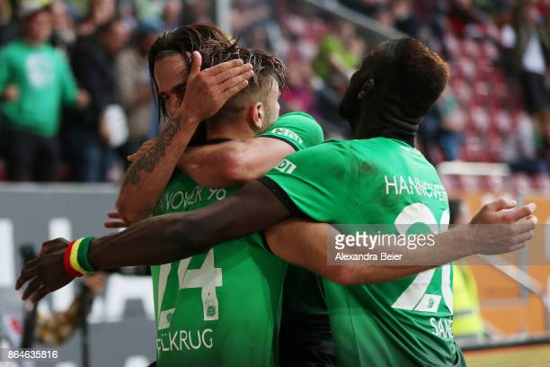 Niclas Fuellkrug of Hannover celebrates with Martin Harnik of Hannover and Salif Sane of Hannover after he scored the winning goal for Hannover to...
