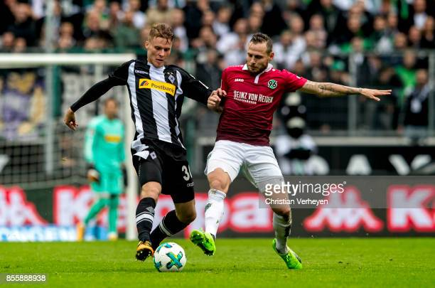 Nico Elvedi of Borussia Moenchengladbach and Marvin Bakalorz of Hannover 96 battle for the ball during the Bundesliga match between Borussia...