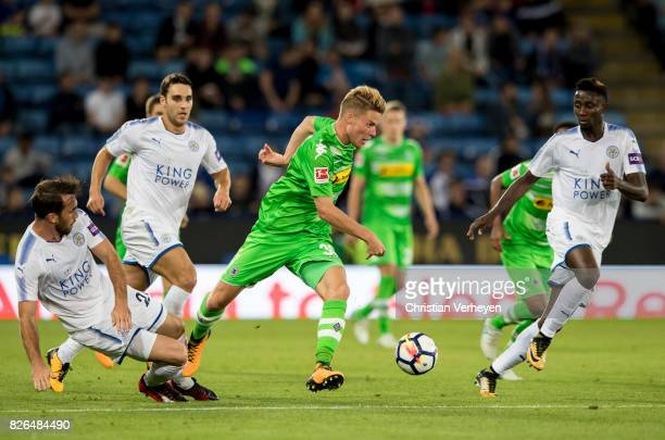 Nico Elvedi of Borussia Moenchengladbach is chased by Christian Fuchs of Leicester City during a friendly match between Leicester City and Borussia...