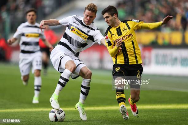 Nico Elvedi of Moenchengladbach and Christian Pulisic of Dortmund battle for the ball during the Bundesliga match between Borussia Moenchengladbach...