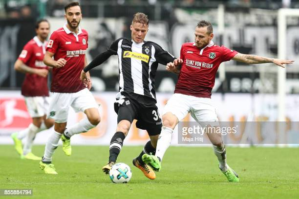 Nico Elvedi of Moenchengladbach and Marvin Bakalorz of Hannover battle for the ball during the Bundesliga match between Borussia Moenchengladbach and...