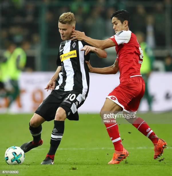 Nico Elvedi of Moenchengladbach fights for the ball with Yoshinori Muto of Mainz during the Bundesliga match between Borussia Moenchengladbach and 1...