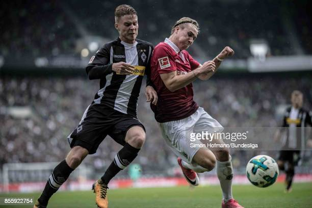 Nico Elvedi of Moenchengladbach is tackled by Felix Klaus of Hannover during the Bundesliga match between Borussia Moenchengladbach and Hannover 96...