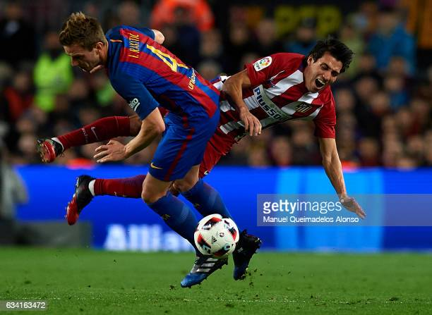 Nico Gaitan of Atletico de Madrid is tackled by Ivan Rakitic of Barcelona during the Copa del Rey semifinal second leg match between FC Barcelona and...