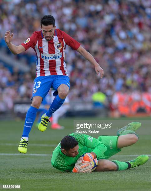 Nico Gaitan of Atletico de Madrid jumps as Salvatore Sirigu goalkeeper of Osasuna catches the ball on the ground during of the match between Atletico...