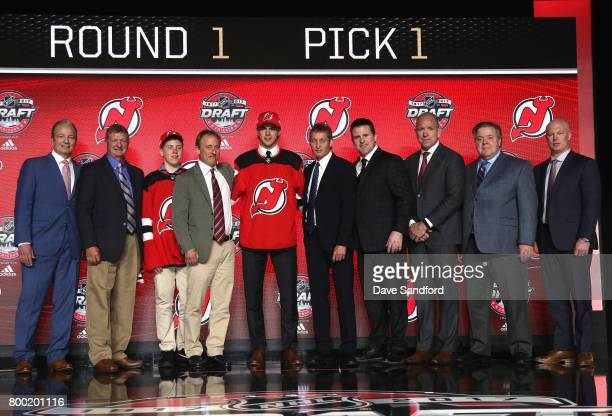 Nico Hischier first overall pick of the New Jersey Devils poses onstage for a photo with the New Jersey Devils draft team during Round One of the...
