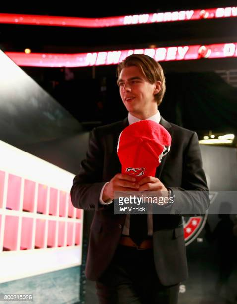Nico Hischier first overall pick of the New Jersey Devils puts on his hat prior to taking the stag during Round One of the 2017 NHL Draft at United...
