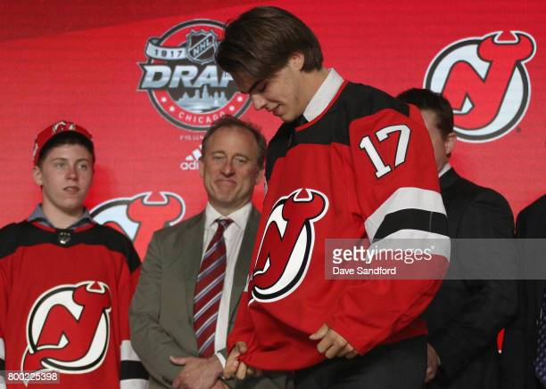 Nico Hischier first overall pick of the New Jersey Devils puts on his jersey onstage during Round One of the 2017 NHL Draft at United Center on June...
