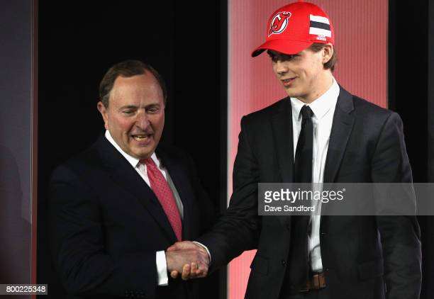 Nico Hischier first overall pick of the New Jersey Devils shakes the hand of NHL Commissioner Gary Bettman onstage during Round One of the 2017 NHL...