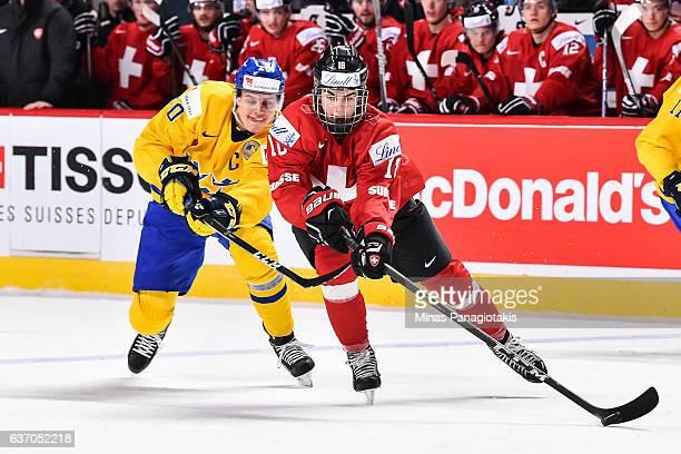 Nico Hischier of Team Switzerland skates the puck against Joel Eriksson Ek of Team Sweden during the 2017 IIHF World Junior Championship preliminary...
