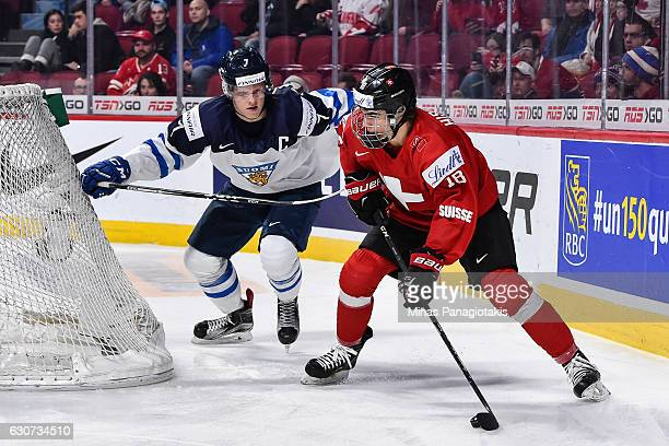 Nico Hischier of Team Switzerland tries to play the puck past Olli Juolevi of Team Finland during the 2017 IIHF World Junior Championship preliminary...