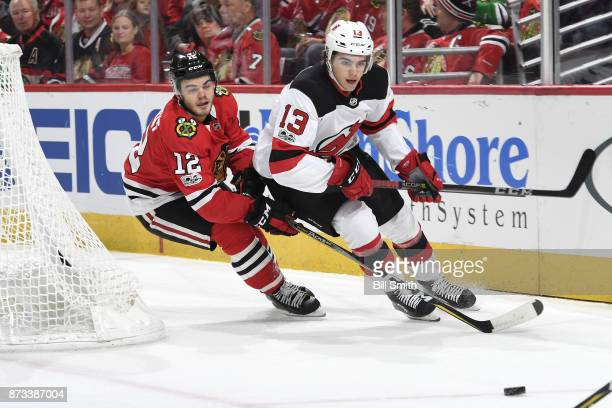 Nico Hischier of the New Jersey Devils and Alex DeBrincat of the Chicago Blackhawks chase the puck in first period at the United Center on November...
