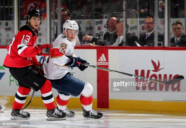Nico Hischier of the New Jersey Devils and Dryden Hunt of the Florida Panthers fight for position on November 11 2017 at Prudential Center in Newark...