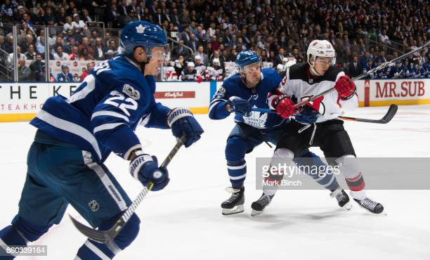 Nico Hischier of the New Jersey Devils battles with Leo Komarov of the Toronto Maple Leafs as Nikita Zaitsev of the Toronto Maple Leafs skates to the...