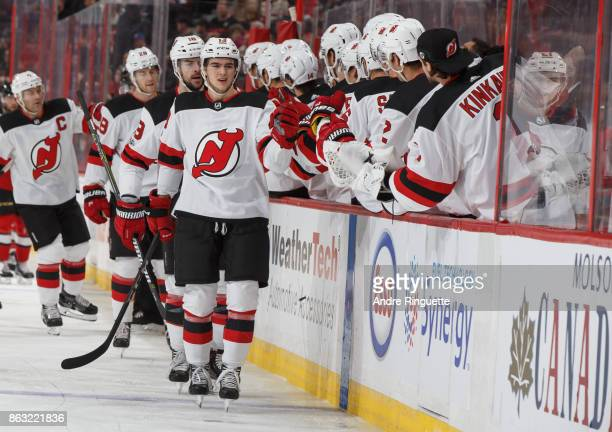 Nico Hischier of the New Jersey Devils celebrates his first career NHL goal with teammates at the players bench against the Ottawa Senators at...
