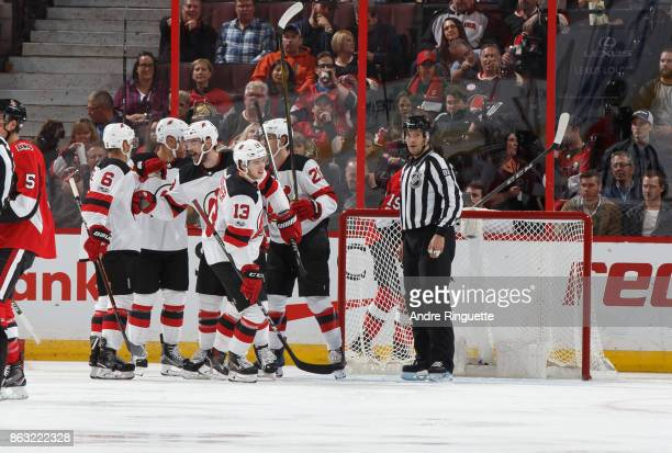 Nico Hischier of the New Jersey Devils celebrates his first career NHL goal with teammates against the Ottawa Senators at Canadian Tire Centre on...