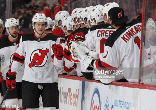 Nico Hischier of the New Jersey Devils celebrates his second career NHL goal and second of the game with teammates at the players bench against the...