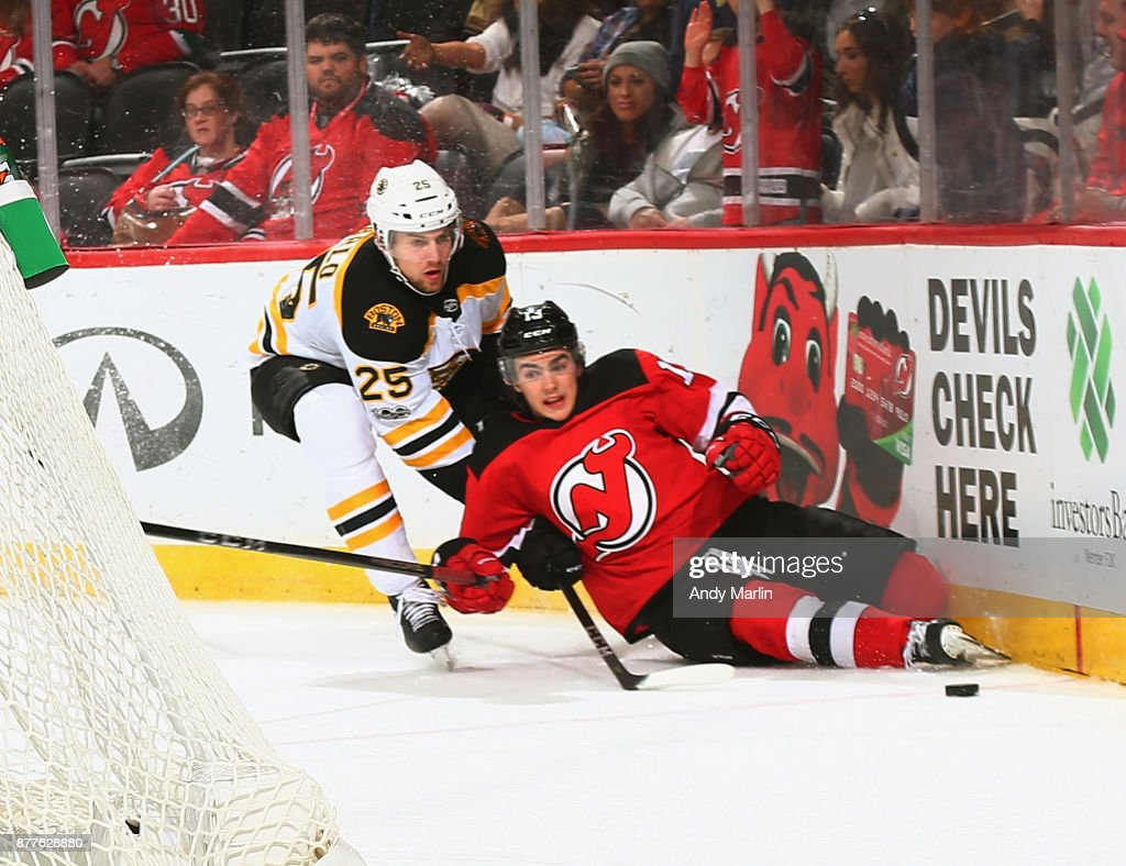 Nico Hischier #13 of the New Jersey Devils is taken down by Brandon Carlo #25 of the Boston Bruins during the game at Prudential Center on November 22, 2017 in Newark, New Jersey.