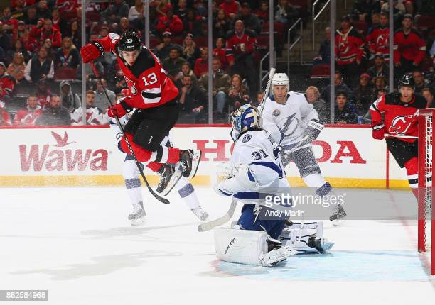 Nico Hischier of the New Jersey Devils jumps to screen Peter Budaj of the Tampa Bay Lightning during the game at Prudential Center on October 17 2017...