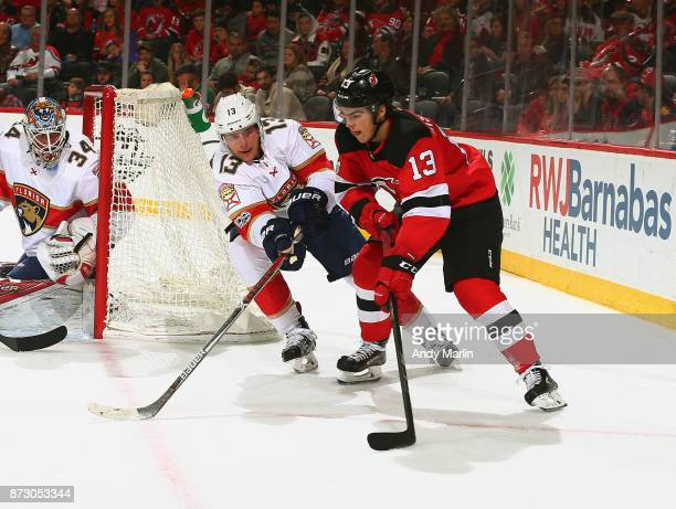 Nico Hischier of the New Jersey Devils plays the puck while being defended by Mark Pysyk of the Florida Panthers during the game at Prudential Center...