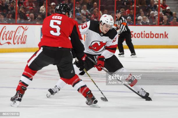 Nico Hischier of the New Jersey Devils stickhandles the puck against Cody Ceci of the Ottawa Senators at Canadian Tire Centre on October 19 2017 in...
