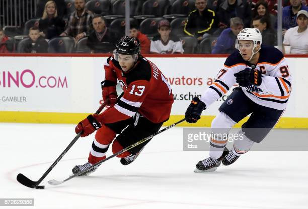 Nico Hischier of the New Jersey Devils takes the puck as Connor McDavid of the Edmonton Oilers defends on November 9 2017 at Prudential Center in...