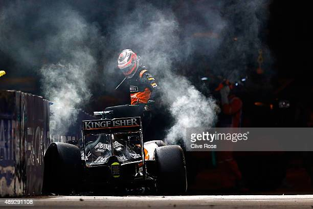 Nico Hulkenberg of Germany and Force India climbs out of his car after crashing during the Formula One Grand Prix of Singapore at Marina Bay Street...