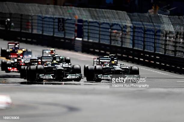 Nico Rosberg of Germany and his team mate Lewis Hamilton of Great Britain and Mercedes GP drive side by side after the start of the Monaco Formula...
