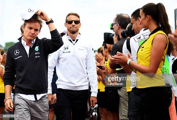 Nico Rosberg of Germany and Mercedes GP and Jenson Button of Great Britain and McLaren Honda arrive for the drivers' parade before the Formula One...