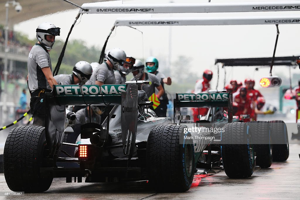 Nico Rosberg of Germany and Mercedes GP and Lewis Hamilton of Great Britain and Mercedes GP drive in for a pitstop during qualifying for the Malaysia Formula One Grand Prix at the Sepang Circuit on March 29, 2014 in Kuala Lumpur, Malaysia.