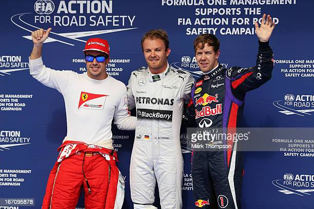 Nico Rosberg of Germany and Mercedes GP celebrates finishing first alongside second placed Sebastian Vettel of Germany and Infiniti Red Bull Racing...