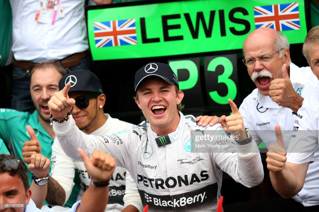 Nico Rosberg of Germany and Mercedes GP celebrates his victory with the team including CEO of Mercedes Dieter Zetsche and Lewis Hamilton of Great Britain and Mercedes GP after the German Grand Prix by at Hockenheimring on July 20, 2014 in Hockenheim, Germany.