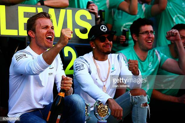 Nico Rosberg of Germany and Mercedes GP celebrates his win with Lewis Hamilton of Great Britain and Mercedes GP and the rest of the team outside the...