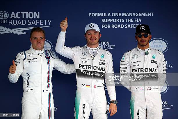 Nico Rosberg of Germany and Mercedes GP celebrates in Parc Ferme next to Lewis Hamilton of Great Britain and Mercedes GP and Valtteri Bottas of...