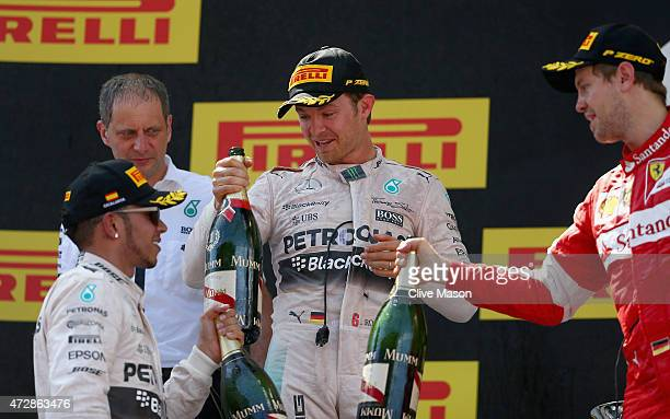 Nico Rosberg of Germany and Mercedes GP celebrates on the podium with Lewis Hamilton of Great Britain and Mercedes GP and Sebastian Vettel of Germany...