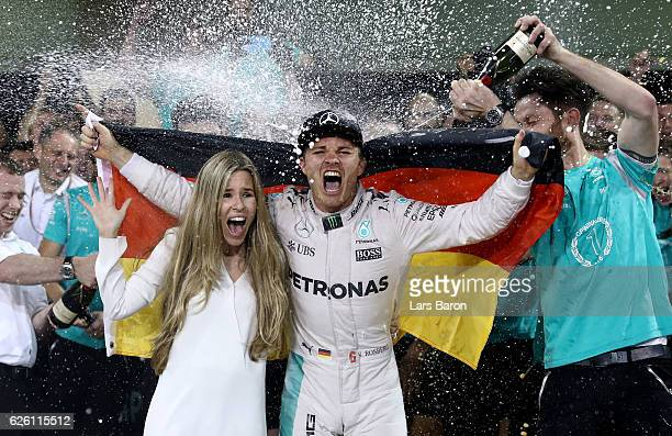 Nico Rosberg of Germany and Mercedes GP celebrates with his wife Vivian Sibold and his team after finishing second and securing the F1 World Drivers...