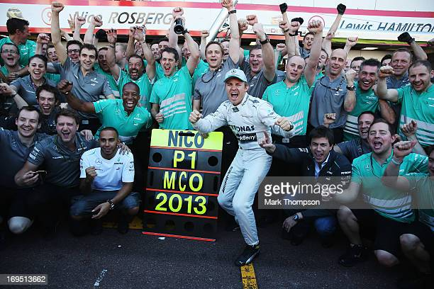 Nico Rosberg of Germany and Mercedes GP celebrates with team mate Lewis Hamilton and the rest of his team after winning the Monaco Formula One Grand...