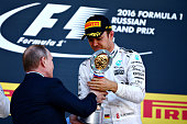 Nico Rosberg of Germany and Mercedes GP collects his winners trophy from Russian President Vladimir Putin on the podium during the Formula One Grand...