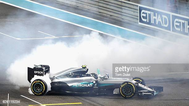 Nico Rosberg of Germany and Mercedes GP does donuts on track after finishing second and securing the F1 World Drivers Championship during the Abu...