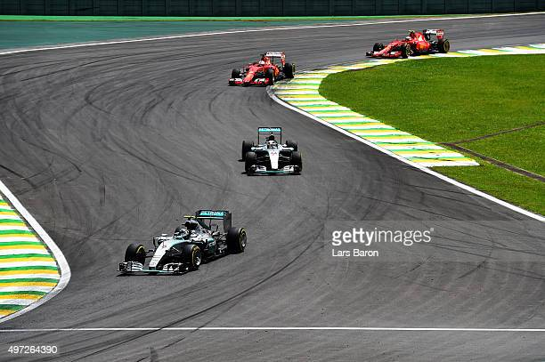 Nico Rosberg of Germany and Mercedes GP drives ahead of Lewis Hamilton of Great Britain and Mercedes GP Sebastian Vettel of Germany and Ferrari and...
